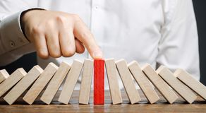 Free Businessman Stops Collapse Domino Effect. Stress Resistance Business. Financial Stability. Recovery Business. Evaluation Of Cash Royalty Free Stock Image - 151860136