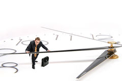 Businessman stops time. Young Businessman with case stops time Royalty Free Stock Photos
