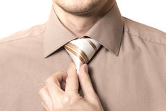 Businessman straightens his tie closeup on white background Stock Photo