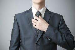 Businessman straightens his tie Stock Image