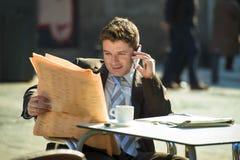 Businessman on street bar having breakfast coffee reading newspaper news talking on mobile phone Royalty Free Stock Images