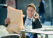 Businessman on street bar having breakfast coffee reading newspaper news talking on mobile phone Royalty Free Stock Image