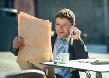 Businessman on street bar having breakfast coffee reading newspaper news talking on mobile phone Stock Image