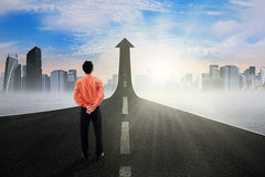 Businessman on the street rising upward. Back view of young businessperson standing on the highway going up as an arrow, symbolizing business growth and Royalty Free Stock Image