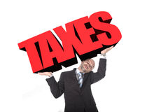 Businessman in stress carrying heavy taxes 3d text word on his arms as a painful burden in tax paying concept Stock Images