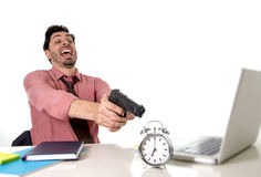 Businessman in stress at office computer desk pointing hand gun to alarm clock in out of time and project deadline expiring. Young attractive businessman in Stock Photo