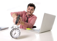 Businessman in stress at office computer desk pointing hand gun to alarm clock in out of time and project deadline expiring Royalty Free Stock Image