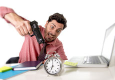 Businessman in stress at office computer desk pointing hand gun to alarm clock in out of time and project deadline expiring Stock Image