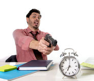 Businessman in stress at office desk pointing hand gun to alarm clock in out of time and project deadline expiring Stock Photos
