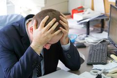 Businessman stressed out at work. Close-up of an office worker. A man in stress in front of a computer. Poor economy concept. Face expression, emotion Stock Photo