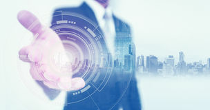 Businessman stretch out hand, with buildings hologram and futuristic interface technology Royalty Free Stock Images
