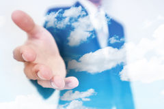 Businessman stretch out hand, with double exposure blue sky and white cloud background Royalty Free Stock Image
