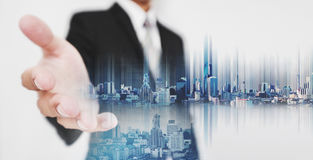 Businessman stretch out hand, with double exposure city, and hologram futuristic city on hand Royalty Free Stock Images