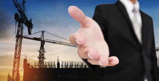 Businessman stretch out hand, with silhouette building construction site in sunrise background Royalty Free Stock Photography