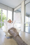 Businessman stretched out in armchair, arms behind head, low angle view Royalty Free Stock Photo