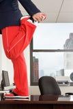 Businessman stretching on desk Stock Photo