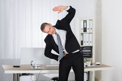 Businessman Stretching In Office Royalty Free Stock Images