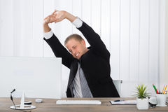 Businessman Stretching In Office Royalty Free Stock Photo
