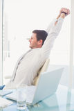 A businessman stretching in swivel chair Stock Image