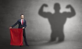 Businessman with strong hero shadow and toreador concept royalty free stock photos