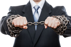 Businessman struggles metal chain tied hands Stock Images