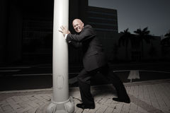 Businessman struggling. Businessman trying to push down a light pole Stock Photography