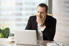 Businessman struggling with drowsiness at work Stock Image