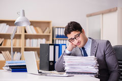 The businessman struggling with stacks of papers Royalty Free Stock Photo
