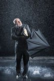 Businessman Struggling To Open Umbrella In Rain Stock Photos