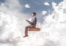 Businessman or student reading book and paper planes flying arou. Young businessman sitting on floating in air book with one in hands Stock Photography