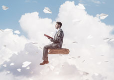 Businessman or student reading book and paper planes flying arou. Young businessman sitting on floating in air book with one in hands Royalty Free Stock Photos