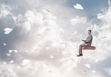 Businessman or student reading book and paper planes flying arou. Young businessman sitting on floating in air book with one in hands Royalty Free Stock Image