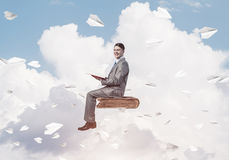 Businessman or student reading book and paper planes flying arou. Young businessman sitting on floating in air book with one in hands Stock Photo