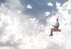 Businessman or student reading book and paper planes flying arou. Young businessman sitting on floating in air book with one in hands Royalty Free Stock Images