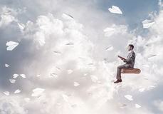 Businessman or student reading book and paper planes flying arou. Young businessman sitting on floating in air book with one in hands Stock Image