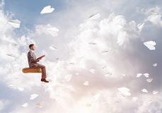 Businessman or student reading book and paper planes flying around. Young businessman sitting on floating in air book with one in hands Stock Photography