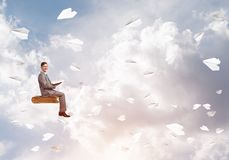 Businessman or student reading book and paper planes flying around. Young businessman sitting on floating in air book with one in hands Stock Image