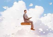 Businessman or student reading book and paper planes flying around. Young businessman sitting on floating in air book with one in hands Stock Photos