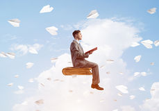 Businessman or student reading book and paper planes flying around. Young businessman sitting on floating in air book with one in hands Stock Photo