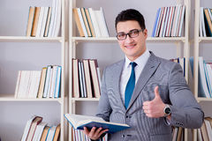 The businessman student reading a book studying in library. Businessman student reading a book studying in library Royalty Free Stock Photo