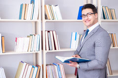 The businessman student reading a book studying in library. Businessman student reading a book studying in library Stock Photos