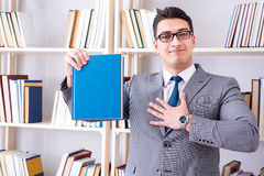 The businessman student reading a book studying in library. Businessman student reading a book studying in library Royalty Free Stock Photography