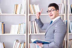 The businessman student reading a book studying in library. Businessman student reading a book studying in library Royalty Free Stock Photos