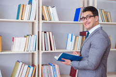 The businessman student reading a book studying in library. Businessman student reading a book studying in library Royalty Free Stock Images