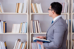 The businessman student reading a book studying in library. Businessman student reading a book studying in library Stock Image