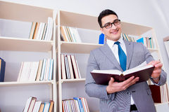 The businessman student reading a book studying in library. Businessman student reading a book studying in library Stock Photography