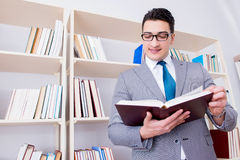 The businessman student reading a book studying in library. Businessman student reading a book studying in library Stock Images