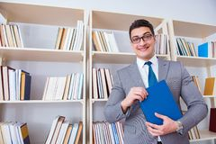 The businessman student reading a book studying in library. Businessman student reading a book studying in library Stock Photo