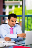 Businessman or student working hard on laptop and writing Stock Images