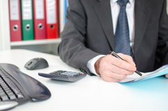 Businessman studying a document Stock Images